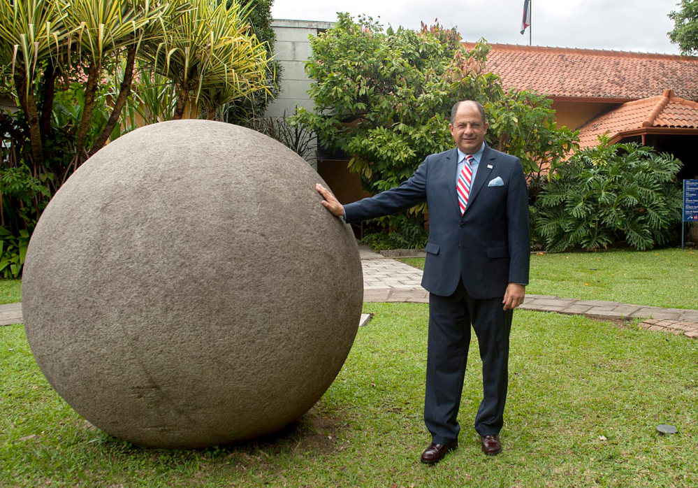 President Solis poses with a stone sphere in San José after four archaeological sites in Southern Costa Rica were added to UNESCO's World Heritage List.